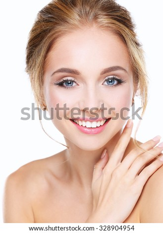 Studio shot of a beautiful young woman with perfect skin against a gray background. - stock photo