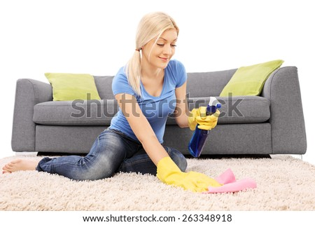 Studio shot of a blond woman cleaning a carpet with a cleaning spray and wearing yellow protective gloves in front of a gray sofa isolated on white background - stock photo