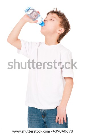 Studio shot of a boy drinks water from a bottle, isolated on white background.