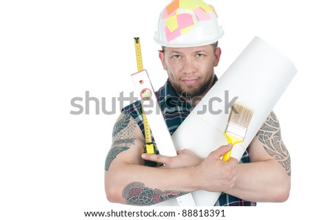 Studio shot of a brawny tattooed foreman in hardhat with various working tools, white background