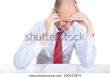 Studio shot of a business man answering a critical call on his cell phone - stock photo