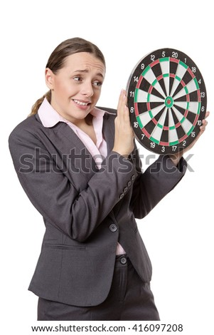 Studio shot of a business woman holding a dartboard out infront of her.  Isolated on a white background