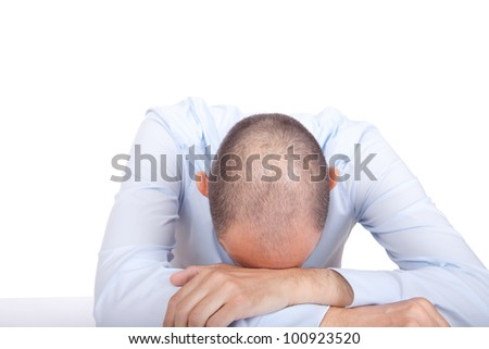 Studio shot of a collapsed business man putting his head on a desk