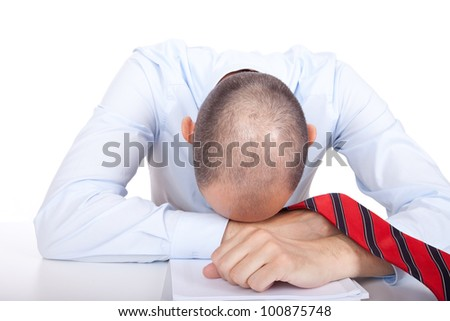 Studio shot of a collapsed business man who puts his head down on a desk