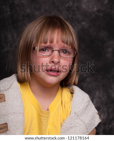 Studio shot of a crying upset child with blonde hair looking disheveled