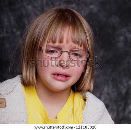Studio shot of a crying upset child with blonde hair looking disheveled - stock photo