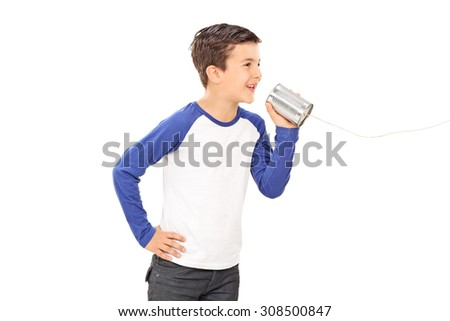 Studio shot of a cute little boy talking through a tin can phone isolated on white background