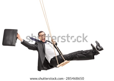 Studio shot of a delighted young businessman swinging on a swing and holding a suitcase isolated on white background - stock photo