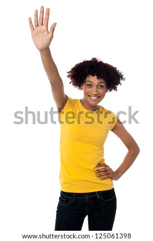 Studio shot of a fashionable young woman waving her hand at somebody.