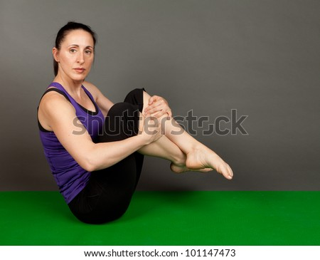 Studio shot of a fit brunette in a paripurna boat yoga pose on a grey background