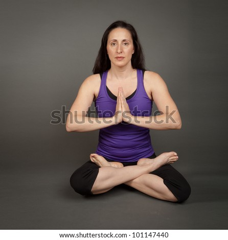 Studio shot of a fit brunette woman in a padma, lotus pose on a grey background