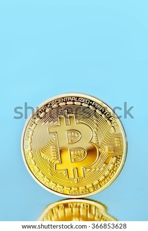 Studio shot of a golden Bitcoin (new virtual money ) on a blue background - stock photo