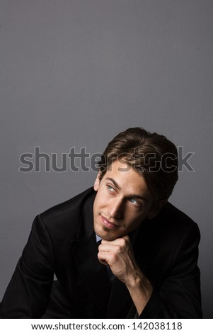 Studio shot of a good looking male model posing as a cool businessman, isolated on gray. - stock photo