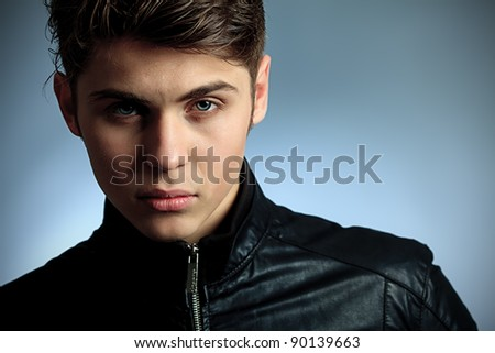 Studio shot of a handsome young man over gray background. - stock photo