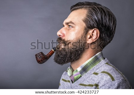 Studio shot of a handsome young man with retro look smoking pipe over gray background