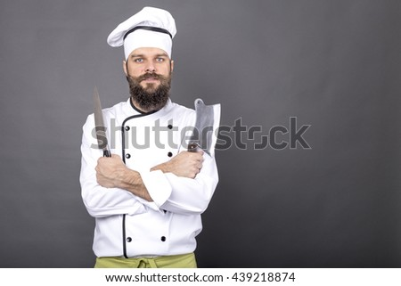 Studio shot of a happy bearded young chef holding sharp knives over gray background - stock photo