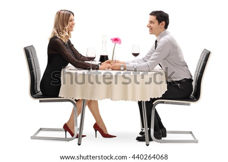 Studio shot of a happy couple sitting on a romantic date and looking at each other isolated on white background - stock photo