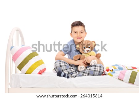 Studio shot of a happy little boy in pajamas, sitting in bed and hugging a teddy bear isolated on white background - stock photo