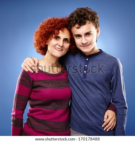 Studio shot of a happy mother and son embracing each other - stock photo