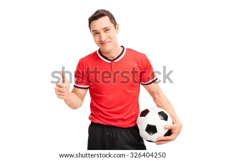 Studio shot of a happy young football player holding a ball and giving a thumb up isolated on white background - stock photo