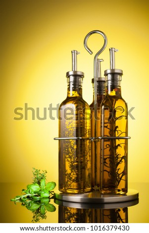 Studio shot of a Homemade olive oil bottle set with spices and herbs (rosemary, peppers, basil, thyme).