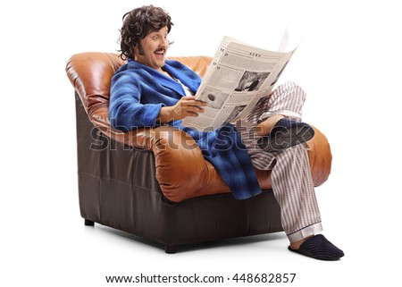 Studio shot of a joyful guy reading a newspaper seated on an armchair isolated on white background