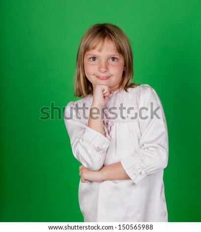 Studio shot of a little girl in a nightgown on green background - stock photo