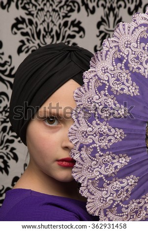 Studio shot of a little girl in a purple dress with a flapper hat and an oriental hand fan