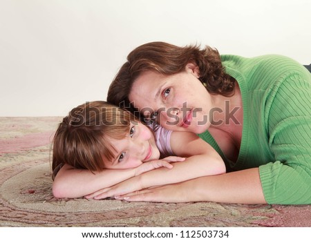 Studio shot of a little girl lying on a carpet being embraced by her mom - stock photo