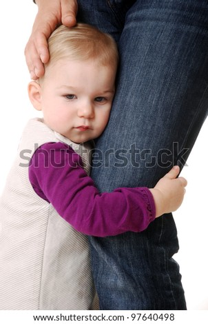 studio shot of a little girl seeking for protection on mothers legs - stock photo