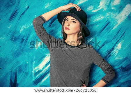 Studio shot of a magnificent young woman in a fitting dress and elegant classic hat. Beauty, fashion concept.