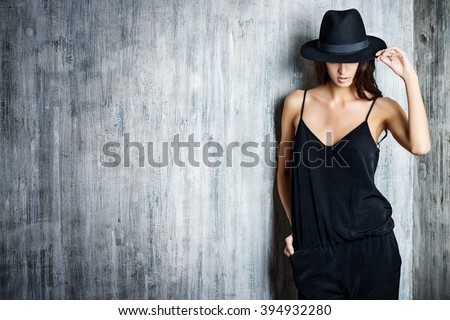 Studio shot of a magnificent young woman in elegant black clothes and classic hat. Beauty, fashion concept. - stock photo