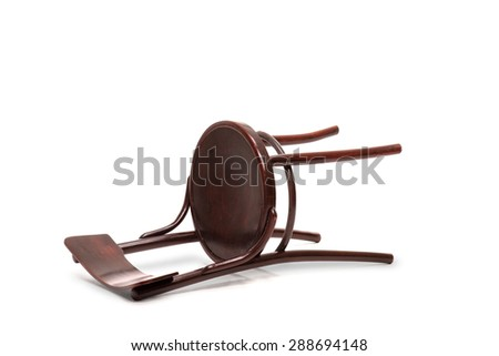 Studio shot of a mahogany brown wooden chair fallen down on the floor isolated on white background - stock photo