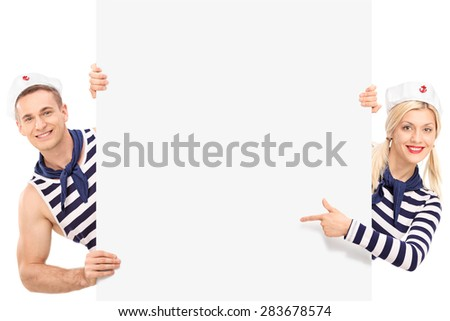 Studio shot of a male and a female sailor posing behind a blank billboard and looking at the camera isolated on white background - stock photo