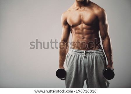 Studio shot of a male model in sweatpants holding dumbbells in both hands on grey background with copy space. Shirtless muscular man working out. Health and fitness theme. - stock photo
