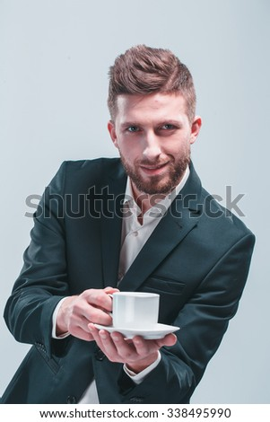 Studio shot of a man with white coffee cup, isolated on gray