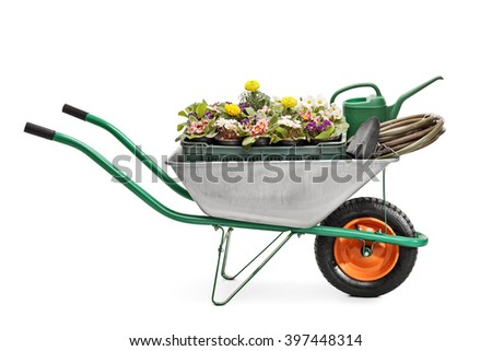 Studio shot of a metal wheelbarrow full of gardening equipment and flowers isolated on white background