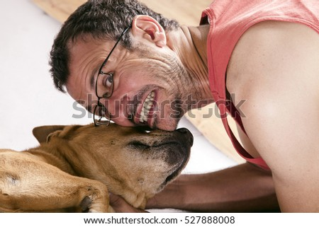 Studio shot of a mixed breed dog on gray background in a moment of affection with its owner.