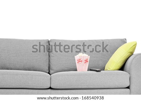 Studio shot of a modern sofa with popcorn box on it isolated on white background - stock photo