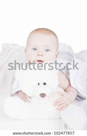 studio shot of a 6 month old baby girl on bed with her teddy bear, isolated on a white background.