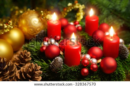 Studio shot of a nice advent wreath with baubles and four burning red candles - stock photo