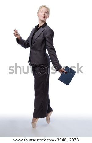 Studio shot of a pretty blonde business model, wearing a suit and ballet shoes, is enpointe whilst holding a closed book in one hand, isolated on a white background.