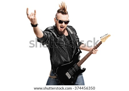 Studio shot of a punk rock guitarist playing guitar and making rock gesture isolated on white background - stock photo