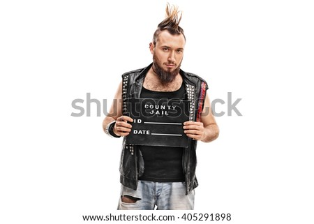 Studio shot of a punk rocker posing for a mug shot with a black plate isolated on white background - stock photo