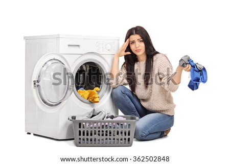 Studio shot of a sad woman emptying a washing machine and looking at the camera isolated on white background - stock photo