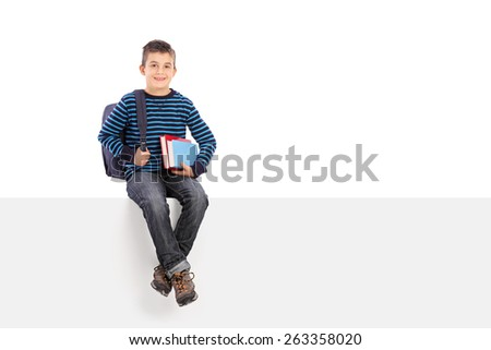 Studio shot of a schoolboy holding a couple of books and carrying a backpack seated on a blank signboard isolated on white background - stock photo