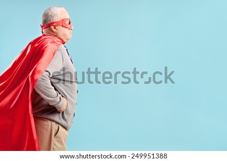 Studio shot of a senior in a superhero outfit on blue background - stock photo