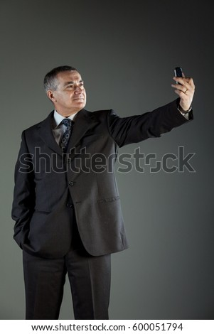 Studio shot of a senior man wearing elegant business suit while taking a selfie with the mobile phone against grey background