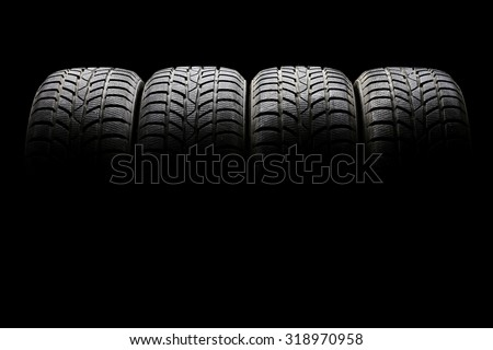 Studio shot of a set of four black car tires lined up horizontally in a dark ambient on black background - stock photo