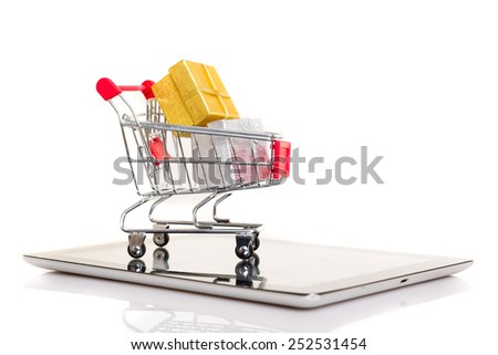 Studio shot of a shopping cart over a tablet computer - stock photo